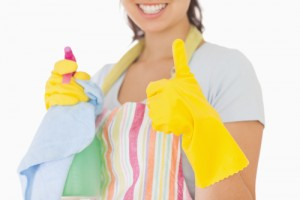 Woman giving thumbs up in rubber gloves holding cleaning products