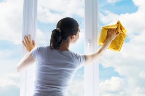 woman washing windows with clouds in the background