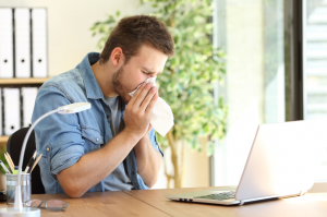 Man sneezing at office desk